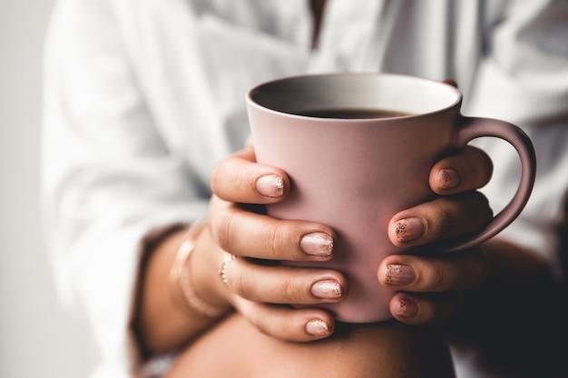 Frau in einem weißen t-shirt hält morgenkaffee in einer rosa keramikschale. maniküre. vorderansicht Premium Fotos
