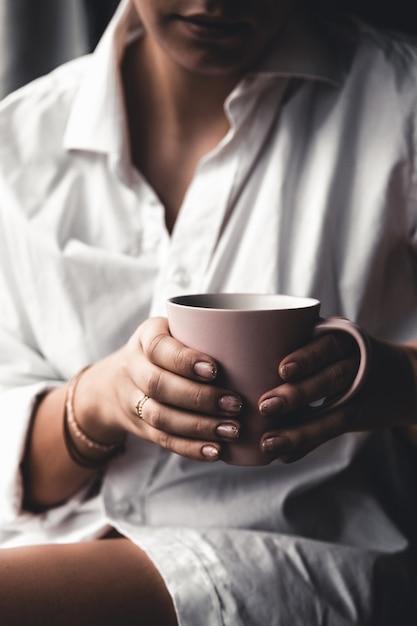 Frau in einem weißen t-shirt hält morgenkaffee in einer rosa keramikschale. Premium Fotos