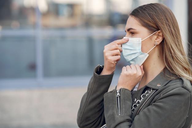 Frau in einer maske steht auf der straße Kostenlose Fotos