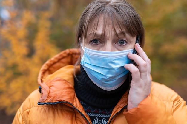 Frau in einer medizinischen maske geht in den herbstpark Premium Fotos