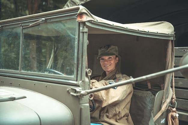 Frau in einer militäruniform in einem armeeauto Premium Fotos