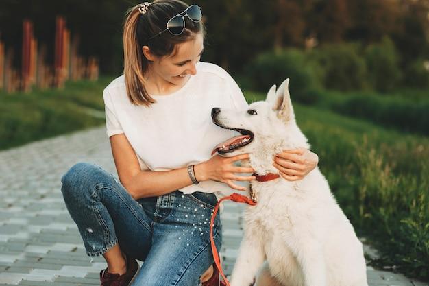 Frau in freizeitkleidung und weißer hund sitzen zusammen auf dem bürgersteig im park und umarmen sich und schauen sich an Premium Fotos