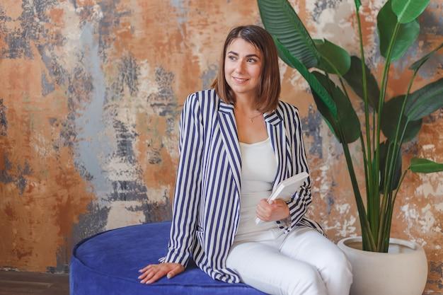Frau in gestreifter aufgebockter aufstellung vor großer anlage. inneninnenporträt. Premium Fotos