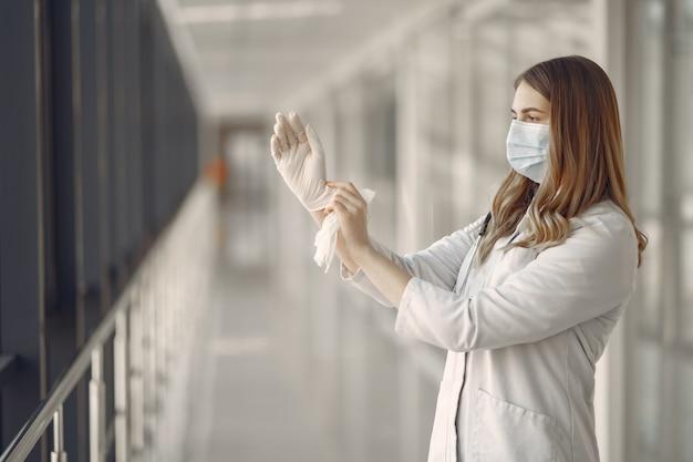 Frau in maske und uniform zieht handschuhe an Kostenlose Fotos
