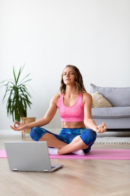 Frau in online-yoga-lektion Premium Fotos