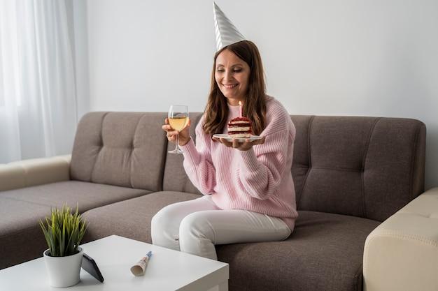Frau in quarantäne mit kuchen und getränk, die geburtstag feiern Premium Fotos