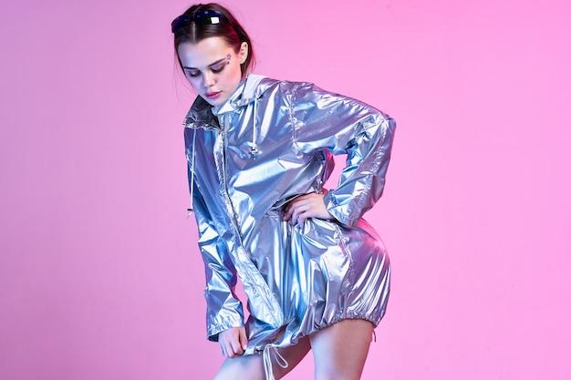 Frau in silbernen kleidern auf einem rosa hintergrund Premium Fotos