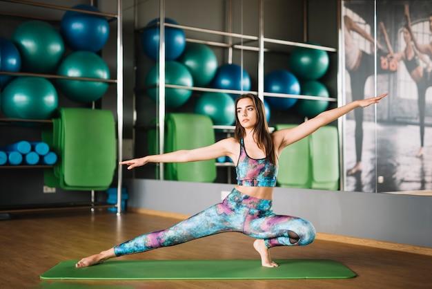 Frau in übendem yoga der sportkleidung in der turnhalle Kostenlose Fotos
