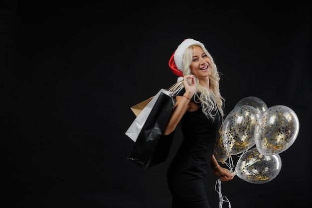 Frau in weihnachtsmütze. weihnachtsfeier auf schwarzer wand, einkaufstaschen und goldenen luftballons Premium Fotos