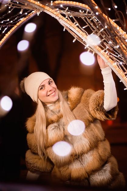 Frau in winterkleidung über verschwommene lichter in der nähe Premium Fotos