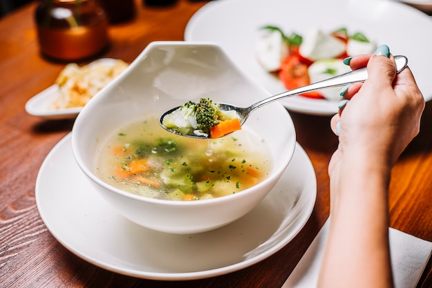 Frau isst gemüsesuppe mit brokkoli, karotte, sellerie und kartoffel Kostenlose Fotos