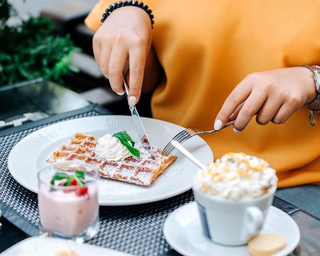 Frau isst waffeln mit sahne belegt Kostenlose Fotos
