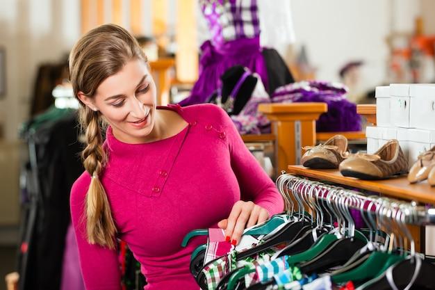 Frau kauft tracht oder dirndl in einem geschäft Premium Fotos