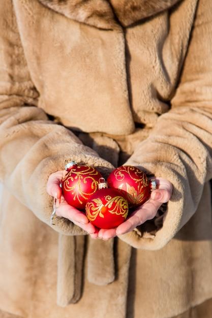 Frau kleidete im pelzmantel an, der in seinen händen drei rote weihnachtsballnahaufnahme, grußkartenkonzept des neuen jahres hält Premium Fotos