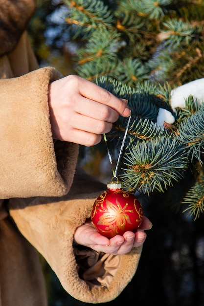 Frau kleidete in einem pelzmantel an, der einen roten weihnachtsball auf tannennahaufnahme hängt Premium Fotos
