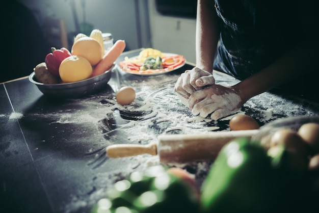 Frau knetet teig für machen pizza auf hölzernem. kochen konzept. Kostenlose Fotos