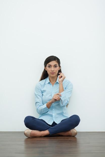 Frau knöpfte an manschette und sitzen auf dem boden Kostenlose Fotos