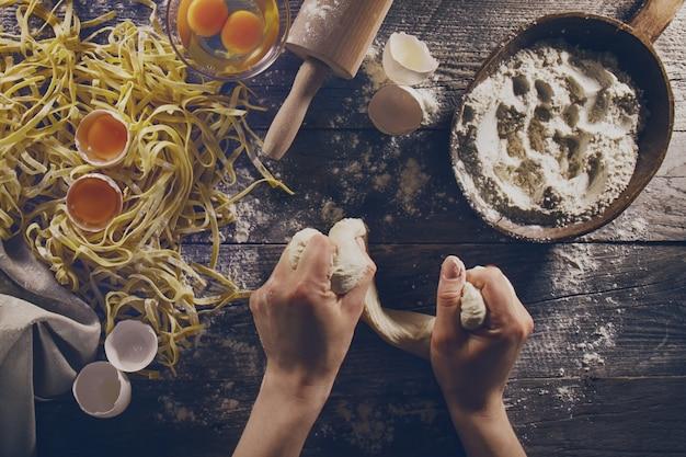 Frau kocht hände vorbereiten leckere hausgemachte klassische italienische pasta auf holztisch. nahansicht. draufsicht. toning Kostenlose Fotos