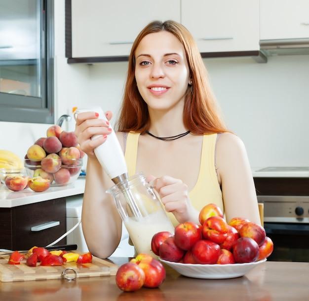 Frau kocht milchgetränke mit nektarinen in der küche Kostenlose Fotos