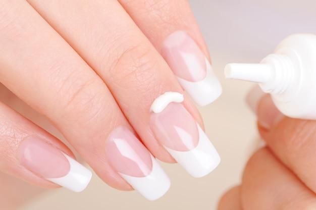 Frau kümmert sich um ihren finger, der die feuchtigkeitsspendende kosmetische creme auf fingernagel anwendet Kostenlose Fotos