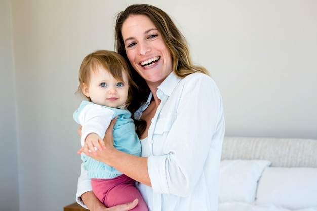 Frau lächelt und hält ein blauäugiges grinsendes baby Premium Fotos