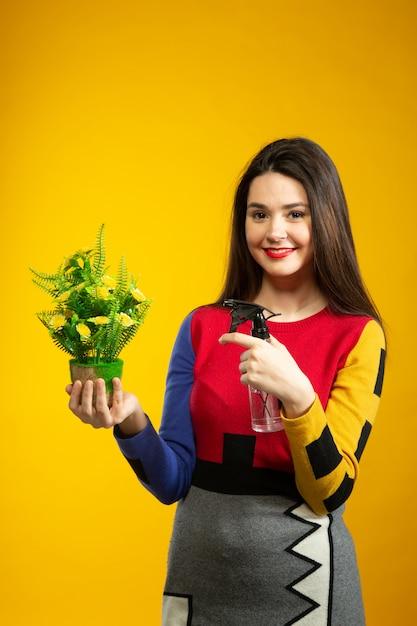 Frau lächelt, während sie mit pflanze aufwirft