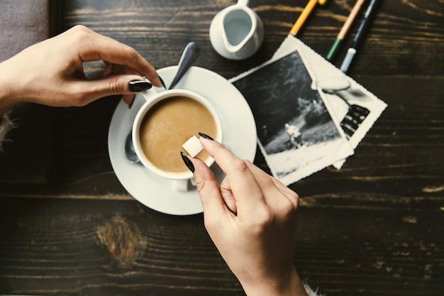 Frau lässt zucker in einen tasse kaffee fallen Kostenlose Fotos