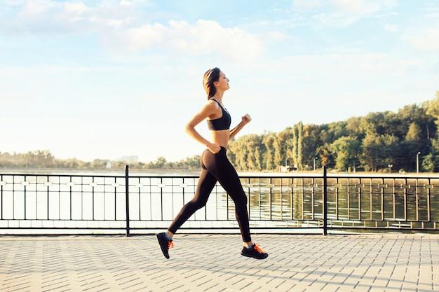 Frau läuft am see bei sonnenuntergang Kostenlose Fotos