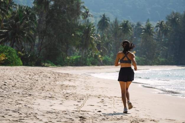 Frau läuft am strand im sommer Premium Fotos