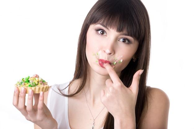 Frau leckt ihre finger beim essen kuchen | Kostenlose Foto
