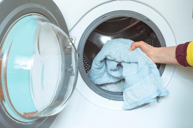 Frau legt schmutzige wäsche in die waschmaschine. Premium Fotos