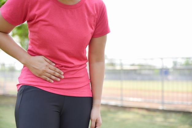 Frau leidet unter bauchschmerzen durch laufen oder training. Premium Fotos