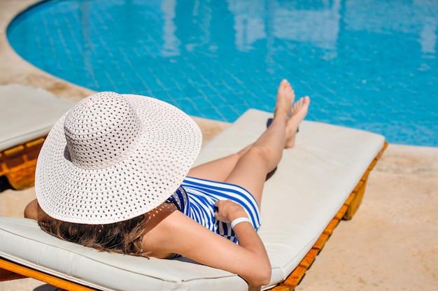 Frau liegt auf einer liege am pool im hotel Premium Fotos