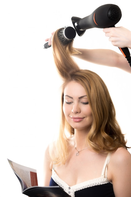 Frau liest ein buch beim kämmen Kostenlose Fotos