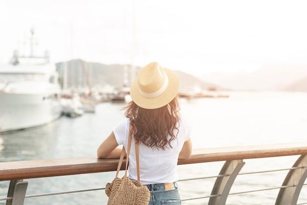Frau lookint bei schiffen auf meer Kostenlose Fotos