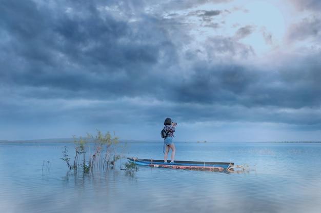 Frau macht ein foto auf dem boot im see Premium Fotos
