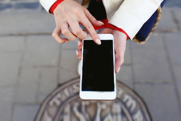 Frau macht ein foto von ihren beinen am telefon Kostenlose Fotos