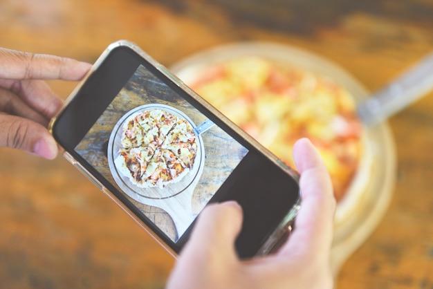 Frau macht foto von ihrer pizza mit smartphone Premium Fotos