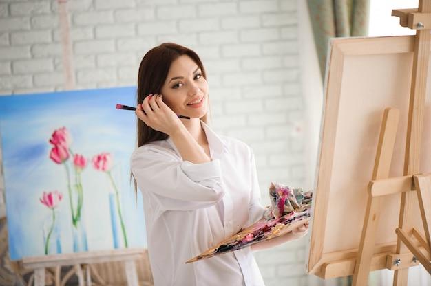Frau malt bild auf leinwand mit ölfarben in ihrem studio Premium Fotos