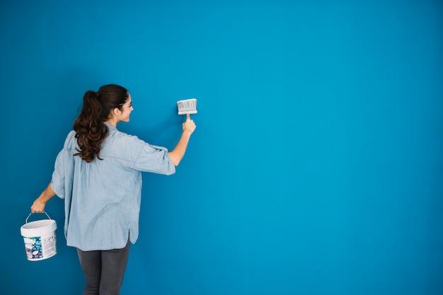 Frau malt blaue wand Kostenlose Fotos