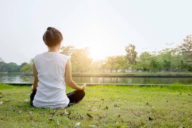 Frau mediation und yoga auf grün archiviert Premium Fotos