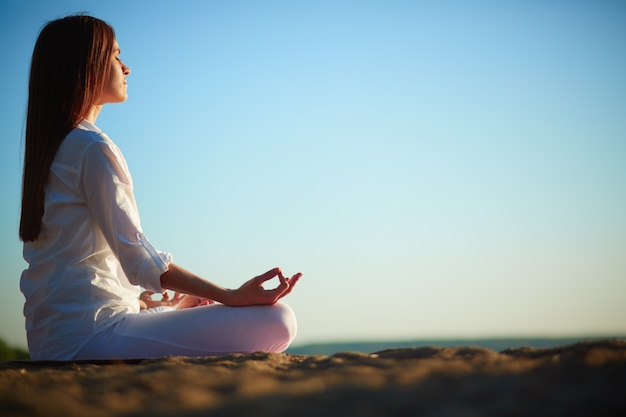 Frau meditiert im lotussitz Kostenlose Fotos