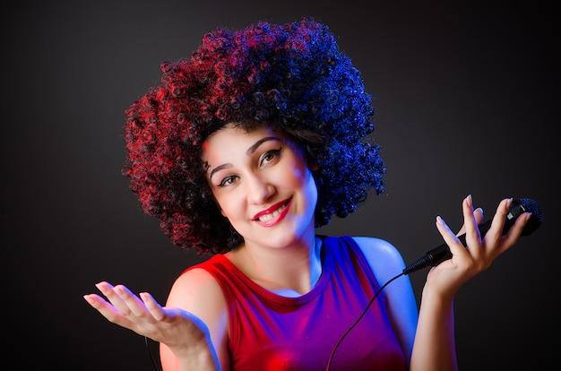 Frau mit afrofrisur singend im karaoke Premium Fotos