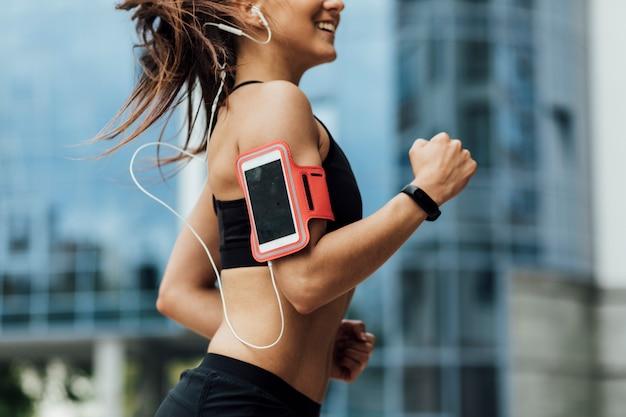Frau mit armbinde und kopfhörer laufen Kostenlose Fotos