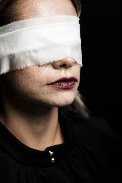 Frau mit augenbinde auf schwarzem hintergrund Kostenlose Fotos