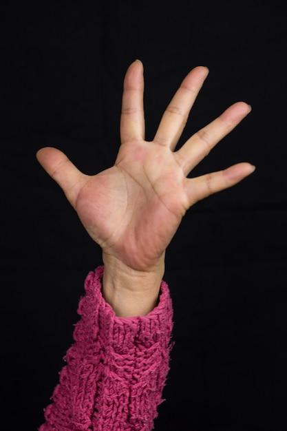 Frau mit ausgestrecktem arm in einem rosa pullover Kostenlose Fotos