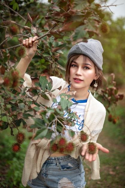 Frau mit bio-rambutanfrucht im obstgarten Premium Fotos