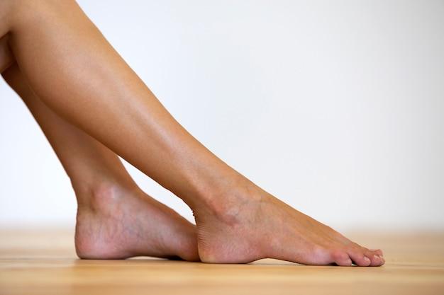 Frau mit bloßen füßen auf dem boden. beinpflege- und hautbehandlungskonzept. Premium Fotos
