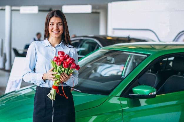 Frau mit blumen in einem autosalon Kostenlose Fotos
