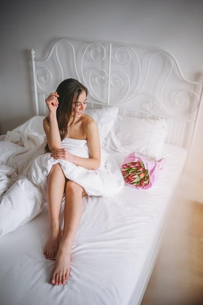Frau mit blumenstrauß von blumen im bett Kostenlose Fotos